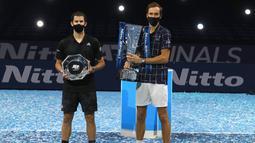 Petenis Rusia Daniil Medvedev (kanan) memegang trofi juara ATP World Finals bersama petenis Austria Dominic Thiem di O2 Arena, London, Inggris, Minggu (22/11/2020). Daniil Medvedev menjuarai ATP World Finals usai mengalahkan Dominic Thiem pada babak final. (AP Photo/Frank Augstein)