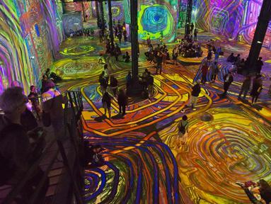Pengunjung menikmati karya pelukis Austria, Friendensreich Hundertwasser di galeri l'Atelier des Lumieres di Paris, Prancis (24/4). Dalam pameran ini pengunjung bisa menikmati lukisan dalam bentuk digital. (AP/Michel Euler)
