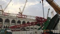 Pekerja dibantu alat berat berusaha mengevakuasi crane yang roboh di Masjidil  Haram, Kota Mekah,  Arab Saudi (9/12/2015). Sebanyak 107 calon jemaah haji meninggal dunia akibat crane jatuh karena cuaca buruk. (AFP PHOTO / STR)