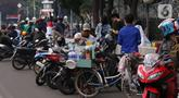 Pedangang membuat minuman untuk massa aksi saat demo penolakan omnibus law di kawasan Patung Kuda, Jakarta, Selasa (20/10/2020). Para pedagang kaki lima memanfaatkan moment aksi massa untuk mencari ke untungan meskipun sangat membahayakan bagi keselamatan mereka. (Liputan6.com/Angga Yuniar)
