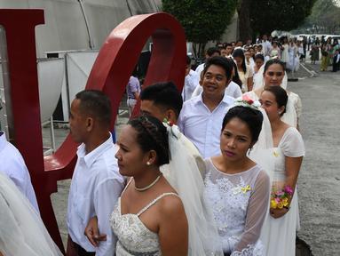 Sejumlah pasangan tiba mengikuti pernikahan massal sebagai bagian dari perayaan Hari Valentine di Manila, Filipina (14/2). Sekitar 200 pasangan dilaporkan ikut serta dalam acara tersebut. (AFP Photo/Ted Aljibe)