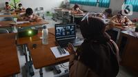 Guru mengajar para murid saat uji coba pembelajaran tatap muka di SDN Malaka Jaya 07 Jakarta, Rabu (9/6/2021). Pembelajaran dilakukan secara campuran antara online (daring) dan tatap muka langsung. (merdeka.com/Imam Buhori)