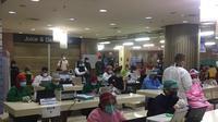 Para petugas bersiap untuk memberikan vaksin Covid-19 ke pedagang Pasar Tanah Abang, Rabu (17/2/2021). (Liputan6.com/Muhammad Radityo Priyasmoro)