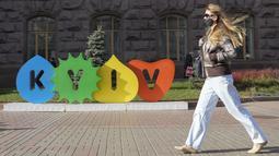 Seorang wanita yang mengenakan masker berjalan di sepanjang Jalan Khreshchatyk utama Kyiv, Ukraina, Kamis (21/10/2021). Infeksi dan kematian virus corona di Ukraina telah melonjak ke level tertinggi sejak pandemi covid-19 di tengah laju vaksinasi yang lamban. (AP Photo/Efrem Lukatsky)