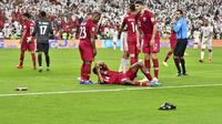 Pemain Qatar, Salem Al Hajri, terbaring karena terkena lemparan sebuah benda saat menghadapi Uni Emirat Arab pada semifinal Piala Asia 2019. Pada laga itu, Qatar menang 2-0 atas UEA. (AFP/Guiseppe Cacace)