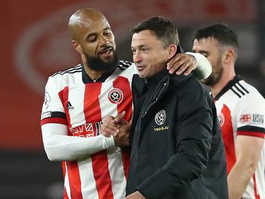 Striker Sheffield United, David McGoldrick (kiri) menghibur manajer interim, Paul Heckingbottom usai kemenangan 1-0 atas Brighton and Hove Albion dalam laga lanjutan Liga Inggris 2020/2021 pekan ke-33 di Bramall Lane, Sheffield, Sabtu (24/4/2021). (AFP/Tim Goode/Pool)