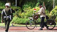 Seorang Veteran Surabaya, menuntun sepeda kuno serta memakai kostum pejuang 45, disapa oleh anggota Polisi Militer TNI AD, saat upacara Hari Pahlawan di Grahadi Surabaya. (Antara)