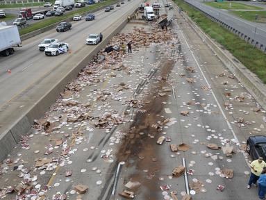 Ratusan pizza beku berserakan di Jalan Raya Arkansas, Amerika Serikat, 9 Agustus 2017. Kejadian disebabkan truk pembawa pizza beku dengan 18 roda kehilangan kendali setelah melintasi jembatan dan terbalik. (Arkansas Department of Transportation via AP)