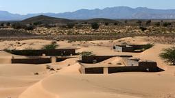Pemandanan rumah-rumah terlantar di Desa Omani, Wadi al-Murr, Oman, 31 Desember 2020. Menurut tetua setempat, semua rumah di desa itu ditelan pasir pada 30 tahun lalu sehingga memaksa penduduk meninggalkan rumah mereka. (MOHAMMED MAHJOUB/AFP)