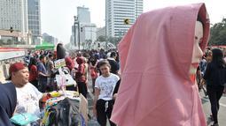 Warga melintasi lapak PKL saat car free day di MH Thamrin, Jakarta, Minggu (8/9/2019). Penutupan sebagian jalan akibat proyek revitalisasi trotoar membuat para PKL menggelar lapak hingga ke badan jalan sehingga menyebabkan aktivitas olahraga warga terhambat. (merdeka.com/Iqbal S. Nugroho)