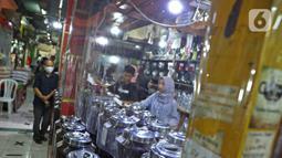 Pembeli sedang berbelanja di Pasar Santa, Jakarta, Selasa (23/6/2020). Plastik pembatas antara pedagang dan pembeli dipasang di kios pasar santa diterapkan dari protokol kesehatan pencegahan COVID-19. (Liputan6.com/Herman Zakharia)