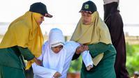 Polisi syariah membawa Nur Fadilah (21) usai dihukum cambuk karena mesum di Banda Aceh, Senin (29/10). Ikhtilat adalah perbuatan bermesraan antara laki-laki dan perempuan yang bukan suami istri dengan kerelaan kedua belah pihak. (Chaideer Mahyuddin/AFP)