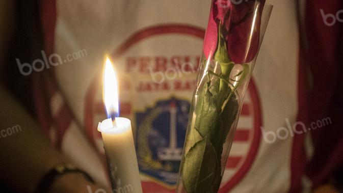 Suporter Persija, The Jakmania, melakukan aksi tabur bunga dan menyalakan lilin mengenang anggotnya Muhammad Fahreza, yang meninggal diduga akibat kekerasan di SUGBK, Jakarta, Senin (16/5/2016). (Bola.com/Vitalis Yogi Trisna)