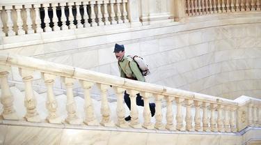 Seorang pria mengenakan seragam militer antik berjalan menaiki tangga Istana Parlemen pada Hari Anak Internasional di Bucharest, Rumania, Selasa (1/6/2021). Lebih dari 10 ribu anak-anak dan orang dewasa mengunjungi gedung era komunis yang juga dikenal House of the People. (AP Photo/Vadim Ghirda)