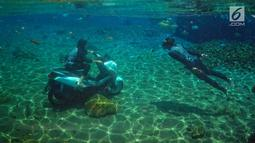 Pengunjung menaiki sepeda motor dalam kolam renang Umbul Ponggok, Desa Polanharjo, Klaten, Jawa Tengah, Minggu (30/9). Umbul Ponggok merupakan mata air yang dimanfaatkan sebagai pemandian dan snorkeling. (Liputan6.com/Gholib)
