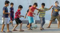 Anak-anak pencari suaka bermain sepak bola di halaman bekas Markas Kodim di Kalideres, Jakarta, Selasa (16/7/2019). Sebelumnya, para pencari suaka dari berbagai negara berkonfilk ini tinggal di pinggir jalan dan trotoar di kawasan Kebon Sirih, Jakarta. (Liputan6.com/Helmi Fithriansyah)