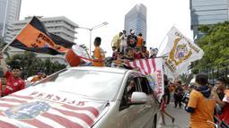 Suporter Persija Jakarta, The Jakmania, konvoi merayakan gelar Piala Liga 1 musim 2018 di Bundaran HI, Jakarta, Sabtu (15/12). Persija berhasil juara Liga 1 usai mengalahkan Mitra Kukar. (Bola.com/Yoppy Renato)