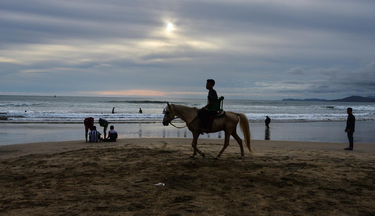 Seorang wisatawan menunggangi kuda saat berlibur Lebaran di Pantai Lhoknga, Aceh Besar, Aceh, Minggu (9/6/2019). (CHAIDEER MAHYUDDIN/AFP)