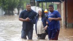 Dua pria membantu seorang wanita menyeberangi jalan yang banjir di Sao Paulo, Brasil, Senin, (10/2/2020). Hujan deras yang membanjiri kota, menyebabkan pinggir sungai utama meluap. (AP Photo/Andre Penner)