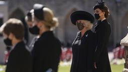 Kate Middletone, Duchess of Cambridge (kanan) berdiri menjelang pemakaman Pangeran Philip di kastil Windsor, Inggris (17/4/2021). Kate Middletone, Duchess of Cambridge tampil memesona dengan busana dan masker hitam. (Victoria Jones/Pool via AP)