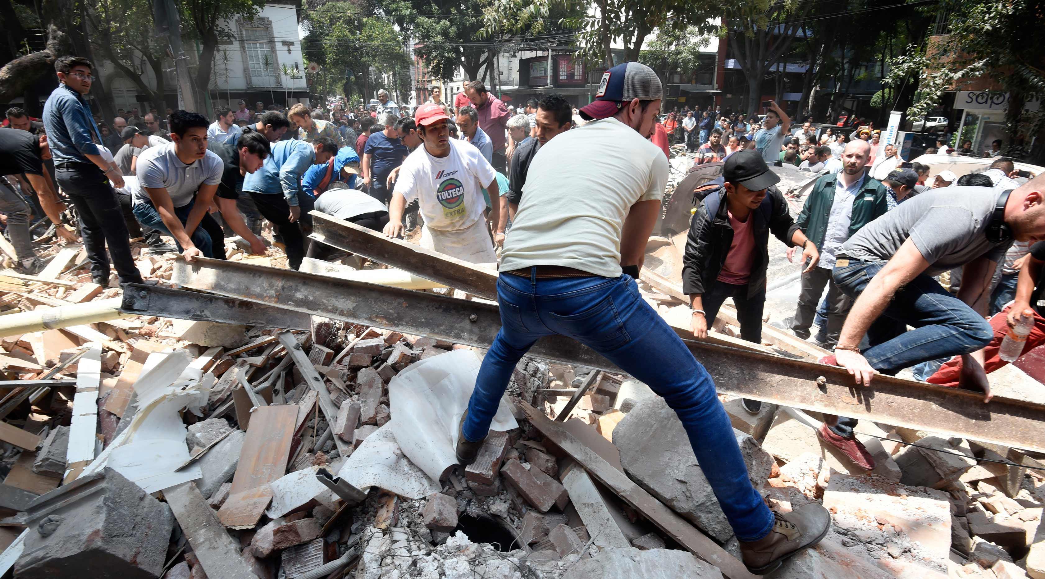 Warga memindahkan puing-puing bangunan untuk mencari korban akibat gempa 7,1 SR di Mexico City, Meksiko (19/9). Sejumlah fasilitas publik seperti bandara, mengalami kerusakan yang signifikan. (AFP Photo/Alfredo Estrella)