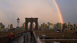 Warga beraktivitas saat pelangi terlihat dari Jembatan Brooklyn di New York City, AS (15/5). Jembatan ini selesai dibangun 1883 dan menghubungkan borough Manhattan dan Brooklyn di New York City melintasi Sungai East. (AFP Photo/Hector Retamal)