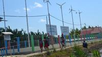 Bocah-bocah Bondan, Ujungalang, Kampung Laut, Cilacap pulang sekolah dan melintas di instalasi energi listrik terbarukan tenaga angin dan matahari. (Foto: Liputan6.com/Muhamad Ridlo).