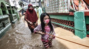 Seorang anak dan wanita berpegangan pada tali saat menyusuri banjir yang merendam permukiman di Kebon Pala, Jakarta, Senin (8/2/2021). Hujan deras yang mengguyur Ibu Kota dan Bogor menyebabkan permukiman di Kebon Pala terendam banjir sejak Minggu (7/2/2021) sore. (merdeka.com/Iqbal S. Nugroho)