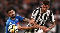 Penyerang Juventus, Mario Mandzukic (kanan) berebut bola dengan bek Napoli, Elseid Hysaj saat bertanding pada lanjutan Liga Serie A Italia di Stadion Allianz di Turin (22/4). Juventus takluk atas Napoli 1-0. (AFP Photo/Marco Bertorello)