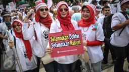 Sejumlah dokter memperlihatkan poster tuntutan saat melakukan aksi unjuk rasa di Ibu Kota hari ini, Senin (24/10). Demo itu untuk menuntut pemerintah agar membatalkan Program Dokter Layanan Primer (DLP). (Liputan6.com/Faizal Fanani)