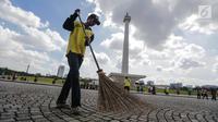 Petugas menyapu membersihkan kawasaan Monas, Jakarta, Senin (1/1). Sebelumnya, kawasan Monas menjadi titik berkumpul warga saat perayaan malam pergantian tahun dan menyisahkan sampah dari pengunjung monas. (Liputan6.com/Faizal Fanani)