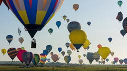 Ratusan balon udara terbang di pangkalan udara Chambley-Bussieres, Hagéville, Prancis, Senin (29/7/2019). Acara itu disebut sebagai salah satu festival balon udara terbesar di dunia. (Jean-Christophe VERHAEGEN/AFP)