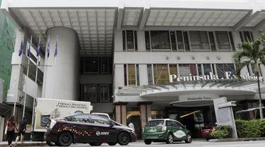 Sejumlah mobil melintas di depan Hotel Peninsula Excelsior, Singapura, Rabu (7/11). Hotel bintang empat ini menjadi tempat menginap Timnas Indonesia jelang Piala AFF 2018. (Bola.com/M. Iqbal Ichsan)