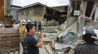 Penduduk dan penyelamat memeriksa bangunan yang rusak setelah gempa bumi yang melanda Padada, provinsi Davao del Sur, Filipina selatan (15/12/2019). Gempa tersebut berkekuatan Magnitudo 6,9. (AP Photo)