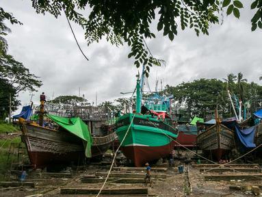 Para pekerja berjalan melewati kapal-kapal yang sedang diperbaiki di galangan kapal di tepi Sungai Yangon, yang terletak di pinggiran Yangon, Myanmar (30/7/2019). (AFP Phot/Sai Aung Main)