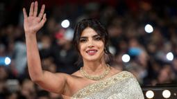 Aktris Priyanka Chopra menyapa penggemarnya saat tiba menghadiri Festival Film Internasional Marrakech ke-18 di Jemaa El Fnaa, Marrakech (5/12/2019). Priyanka Chopra tampil cantik memesona mengenakan busana sari emas dan brokat perak denga dengan kalung emas di lehernya. (AFP/Fadel Senna)