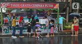 Warga mengantre untuk mendapatkan takjil gratis di Jalan Cempaka Putih Tengah XXI, Jakarta, Rabu (14/4/2021). Berbagai menu takjil dibagikan secara gratis seperti aneka kue, kolak, gorengan, nasi kotak dan lain-lain. (Liputan6.com/Herman Zakharia)