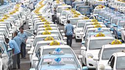 Ratusan taksi parkir di sepanjang silang Monas, Jakarta, (14/3). Mereka menuntut pemerintah menutup transportasi berbasis online yang tidak sesuai dengan Undang-Undang (UU) Nomor 2 Tahun 2009 tentang Lalu Lintas. (Liputan6.com/Immanuel Antonius)
