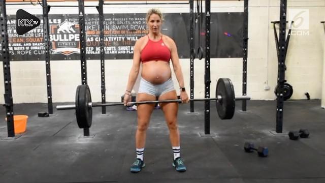 Seorang ibu hamil dengan usia kandungan 7 bulan menjaga kebugaran tubuh dengan olahraga tak biasa. Olahraga yang ia pilih adalah angkat beban.