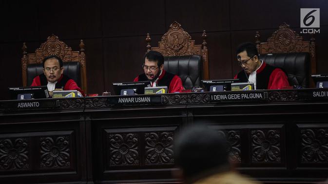 Ketua Mahkamah Konstitusi Anwar Usman (tengah) membuka sidang putusan sengketa hasil Pilpres 2019 di Gedung Mahkamah Konstitusi, Jakarta, Kamis (27/6/2019). Sidang yang dimohonkan Prabowo Subianto-Sandiaga Uno itu beragendakan pembacaan putusan oleh majelis hakim MK. (Liputan6.com/Faizal Fanani)