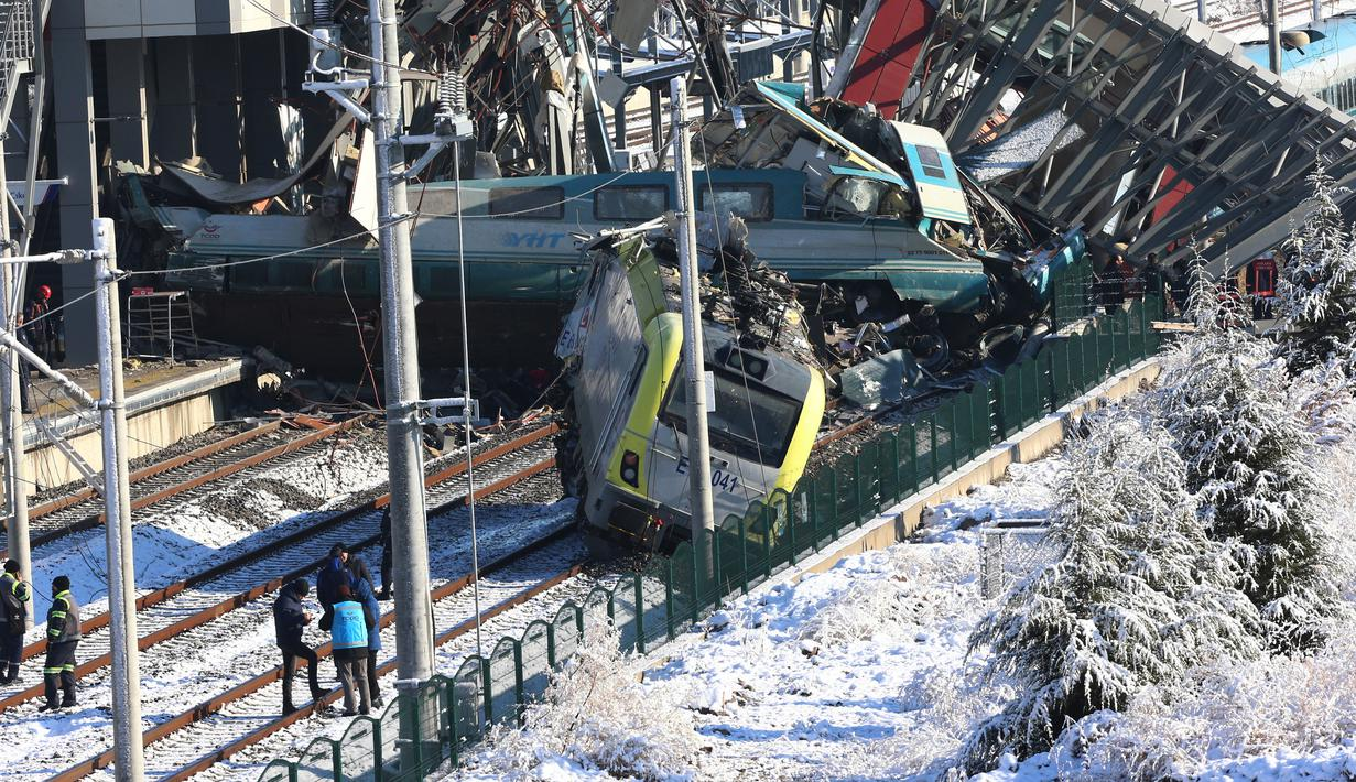 Tim penyelamat bekerja di lokasi kecelakaan kereta di Ankara, Turki, Kamis (13/12). Kereta berkecepatan tinggi tergelincir dari rel dan menabrak lokomotif serta jalan layang di dekat Stasiun Marsandiz. (AP Photo/Burhan Ozbilici)