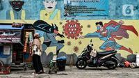 """Warga berjualan di depan mural """"Lawan COVID-19"""" di kawasan zona merah COVID-19 RW 01 Kelurahan Bungur, Jakarta, Rabu (10/2/2021). Pemprov DKI Jakarta mencatat wilayah zona merah COVID-19 melonjak jadi 82 rukun warga (RW). (merdeka.com/Iqbal S. Nugroho)"""