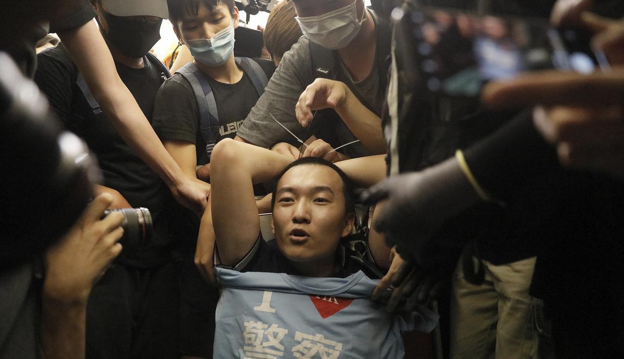 """Para pengunjuk rasa mengikat seorang pria yang mengenakan kaus bertuliskan kata-kata """"Saya suka polisi"""" yang menurut para pengunjuk rasa adalah seorang petugas polisi dari China daratan, saat demonstrasi di Bandara di Hong Kong (13/8/2019). (AP Photo/Vincent Yu)"""