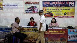 Penjual tiket bus antar provinsi menjaga standnya di Terminal Pulo Gebang, Jakarta, Kamis (8/6). Penjual mengeluhkan sepinya pembelian tiket bus di Pulo Gebang karena masih banyaknya terminal bayangan yang beroperasi. (Liputan6.com/Faizal Fanani)