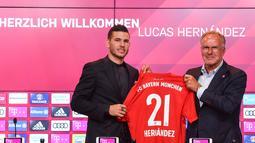Bek baru Bayern Munchen, Lucas Hernandez berpose bersama CEO Bayern Munchen, Karl-Heinz Rummenigge sambil memegang jersey saat diperkenalkan secara resmi di Allianz Arena, Senin (8/7/2019). Pemain 23 tahun ini diikat kontrak selama lima tahun atau hingga 2024 oleh Bayern. (Christof STACHE/AFP)
