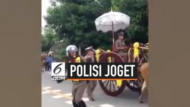 Seorang polisi menarik perhatian publik saat pawai di jalan Ratchaburi, Thailand. Polisi tersebut mengatur lalu lintas pawai sambil berjoget. Aksi kocaknya ini terekam kamera warga.