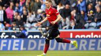 Gelandang Manchester United (MU) Scott McTominay merayakan gol ke gawang Huddersfield Town pada lanjutan Liga Inggris di John Smith's Stadium, Minggu (5/5/2019). (Anthony Devlin/PA via AP)