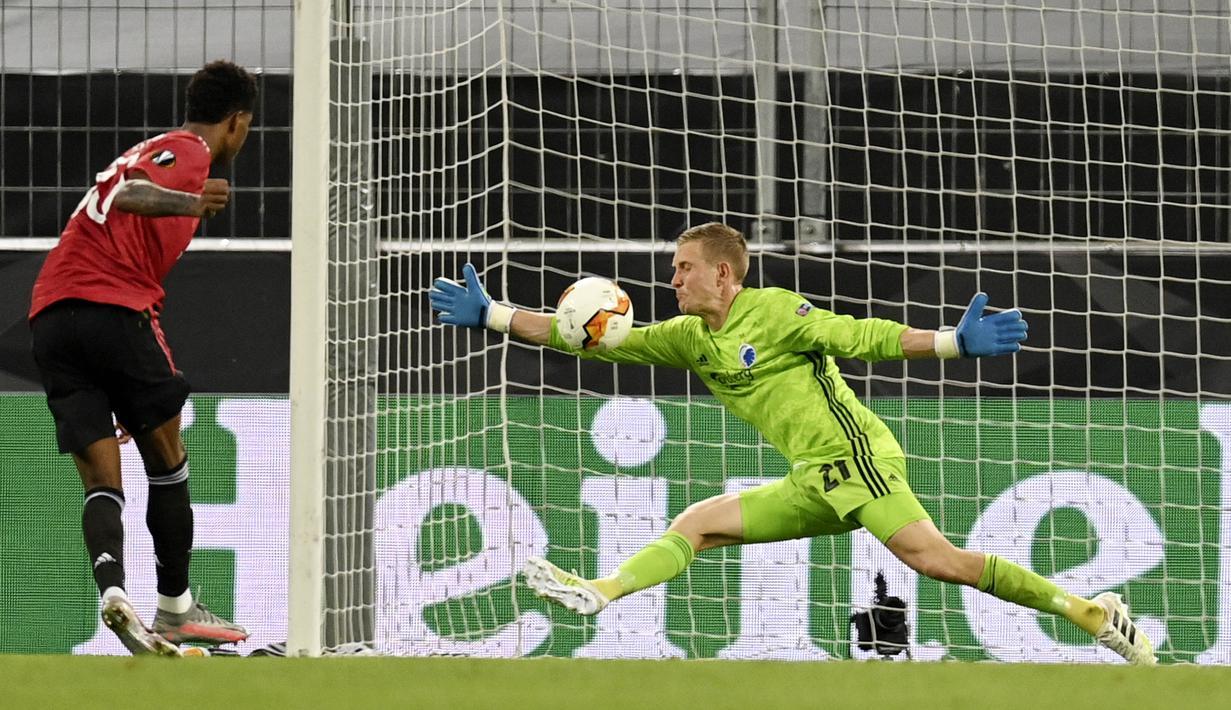 Kiper Copenhagen, Karl-Johan Johnsson, menghalau bola tendangan penyerang Manchester United, Marcus Rashford, pada laga Liga Europa di Stadion Rhein Energie, Senin (10/8/2020). MU menang tipis 1-0 atas Copenhagen. (Sascha Steinbach/Pool via AP)