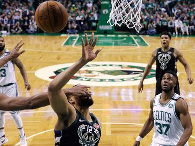 Pemain Boston Celtics, Al Horford (42) menghalau tembakan pemain Milwaukee Bucks, Jabari Parker (12) pada laga playoffs NBA basketball di TD Garden, Boston, (24/4/2018). Celtics menang  92-87. (AP/Charles Krupa)
