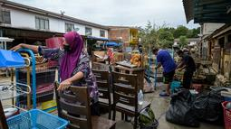 Warga membersihkan barang-barang setelah banjir surut di Mentakab, negara bagian Pahang, Malaysia (11/1/2020). Hujan deras yang terus melanda beberapa bagian jalan raya Pantai Timur di Pahang membuat daerah tersebut terendam banjir parah. (AFP/Mohd Rasfan)